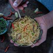 a set of hands holding a bowl of Chilly Garlic Noodles