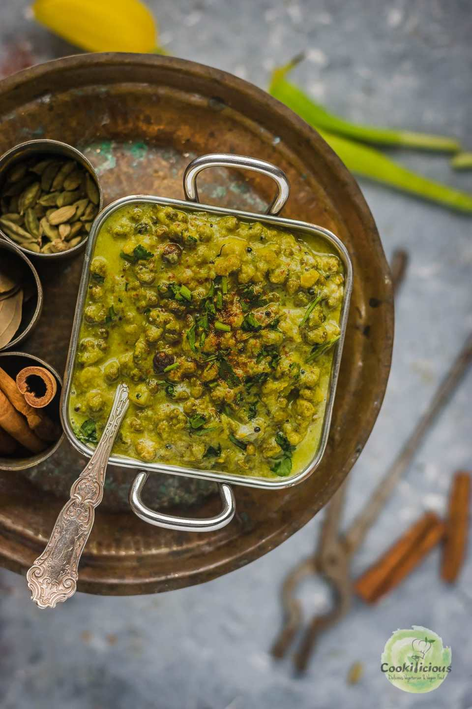 Moong Sprouts Coconut Vegan Curry in a square bowl with a spoon in it