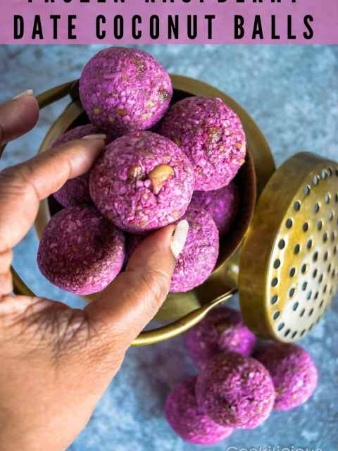 A hand picking up one from the many Frozen Raspberry Date Coconut Balls from a brass bowl and text at the top