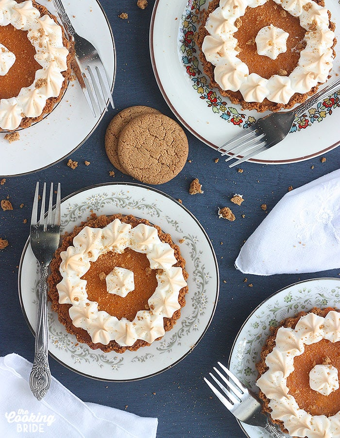 overhead shot of four mini sweet potato tarts on different plates against a blue background