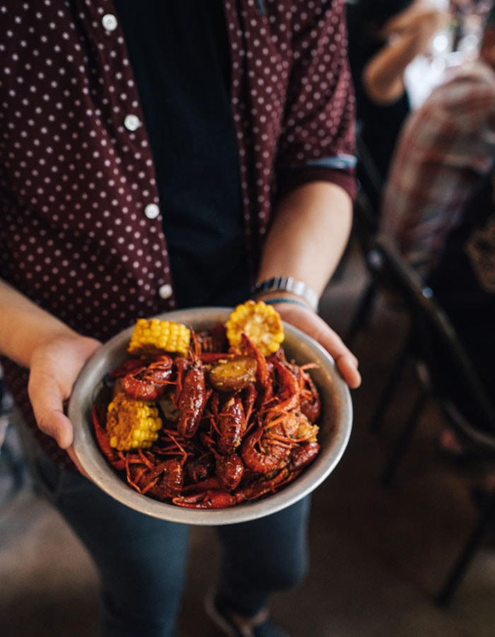 person holding a bowl of crawfish and corn