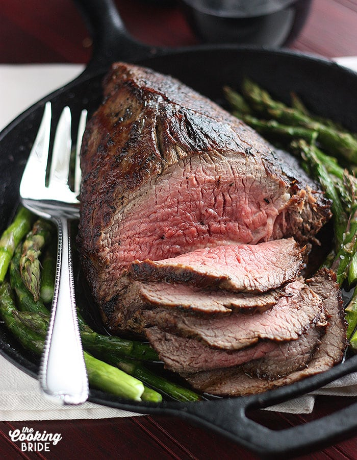 sliced medium rare roast beef with roasted asparagus sitting in a cast iron skillet