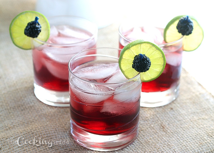 Three blackberry limeade drinks garnished with lime slices and fresh blackberries