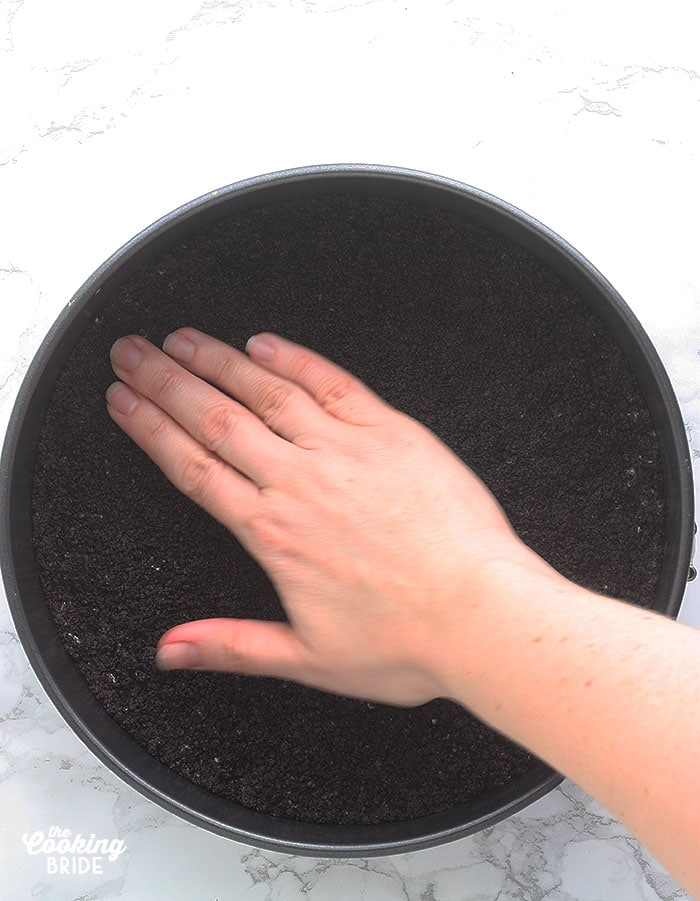 a hand pressing the cookie crumb crust into the bottom of the pan