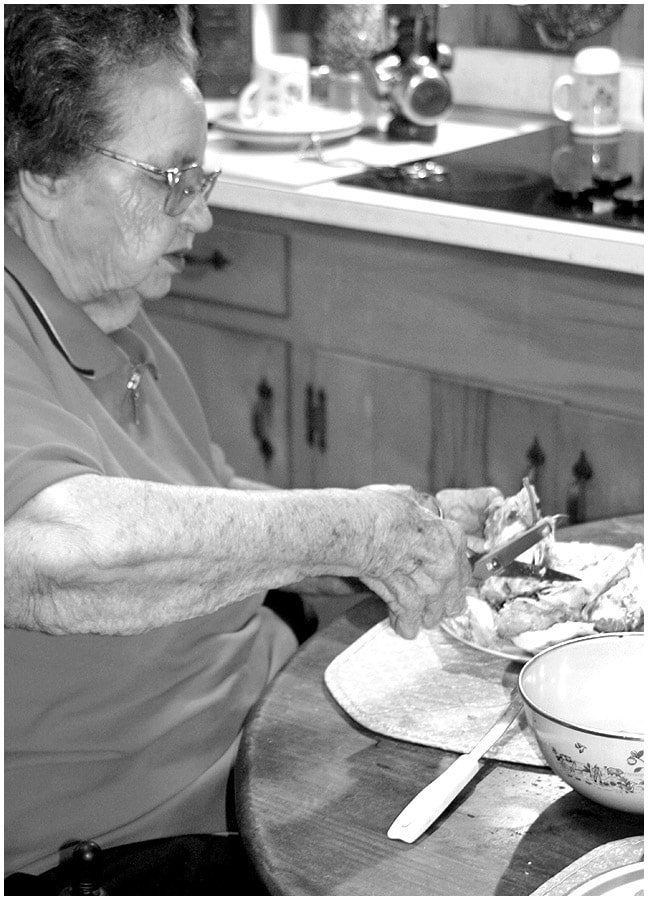 Mamaw sitting at her kitchen table cutting up chicken for her homemade chicken and dumplings.