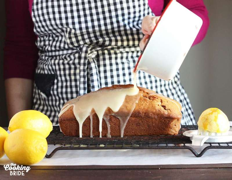 pouring lemon glaze over the cooled loaf cake