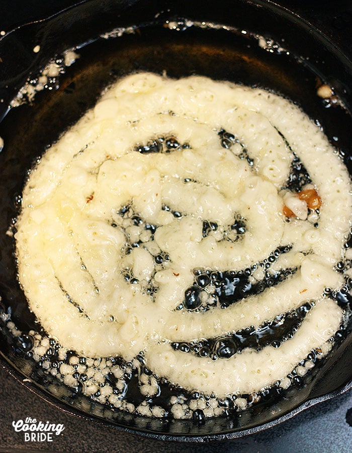 batter frying in hot oil in a cast iron skillet
