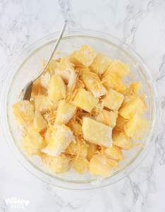 pineapple chunks in a large glass mixing bowl combined with cheese, flour and sugar