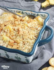 baked pineapple casserole in a blue and white casserole dish on a gray napkin