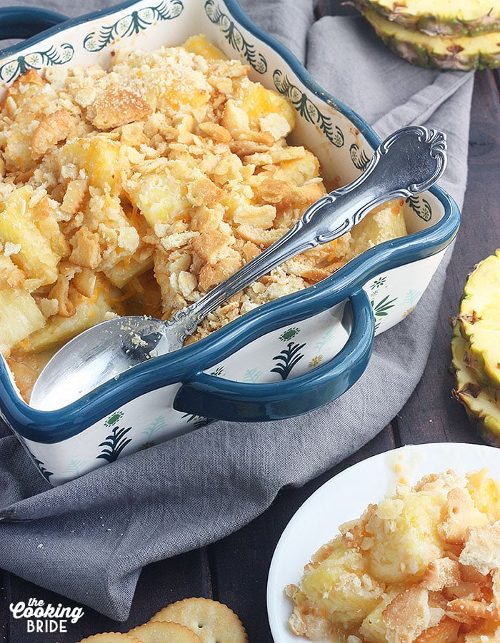 baked pineapple casserole in a blue and white casserole dish with a metal serving spoon and a serving of casserole on the side on a white plate