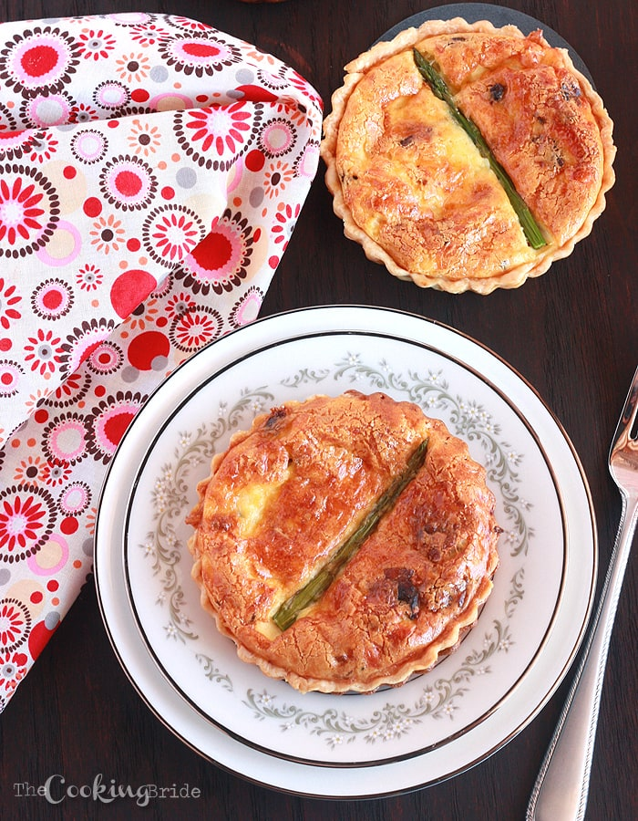 two asparagus quiches on a brown tabletop with a brightly colored napkin in the background