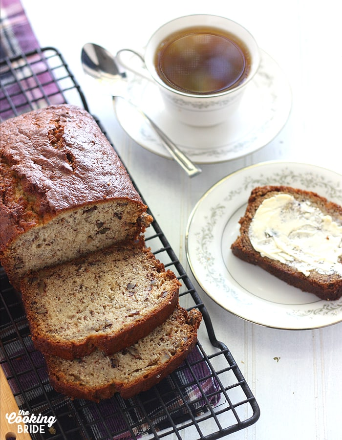 Homemade Banana Bread on a cooling rack with a cup of tea in the background.