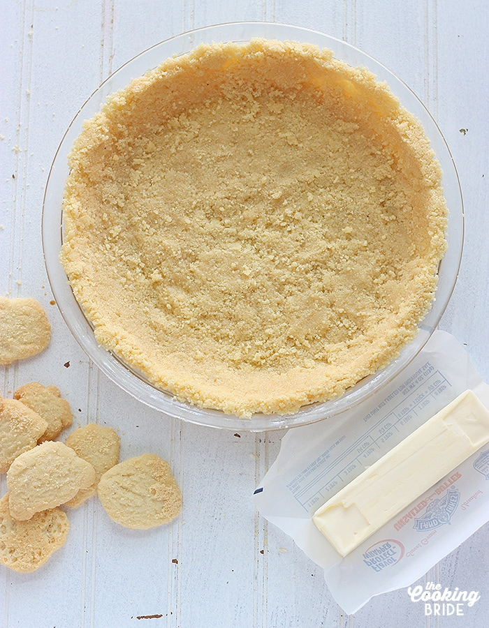 unbaked lime shortbread pie crust with cookies and a stick of butter in the foreground