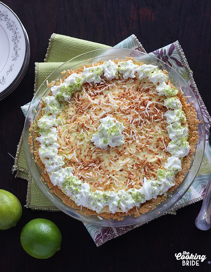overhead shot of coconut lime icebox pie garnished with toasted coconut, whipped cream and lime zest