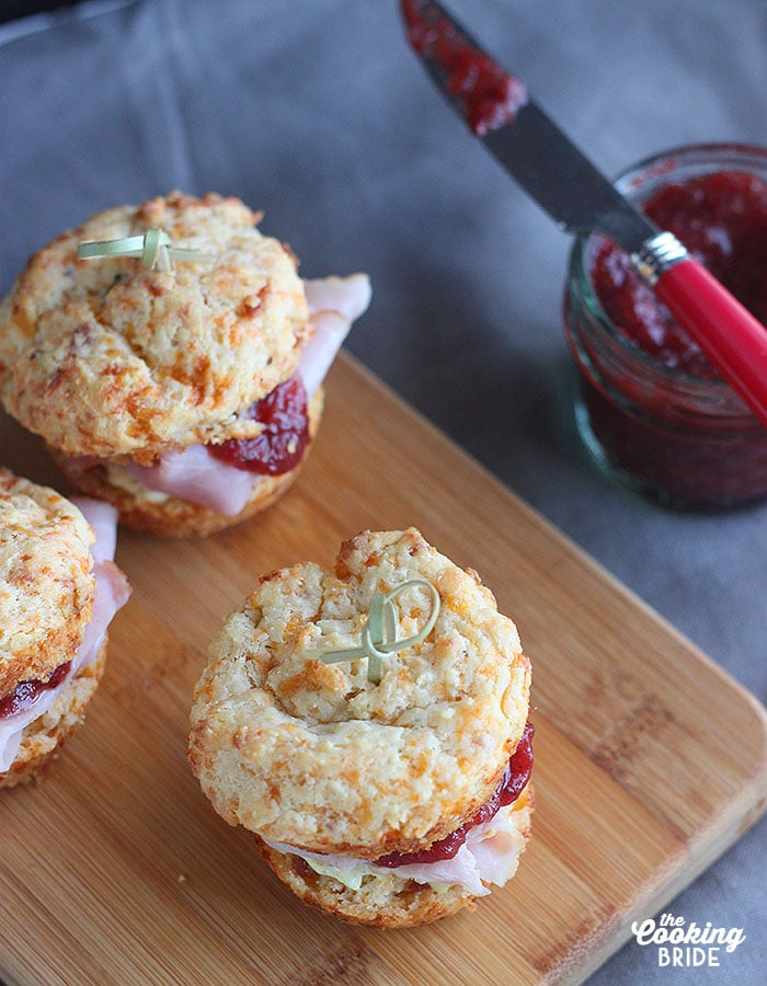 Cheddar bacon muffins are the base of these festive ham sliders. Salty ham is layered with creamy mustard cream cheese spread and spicy cranberry chutney.