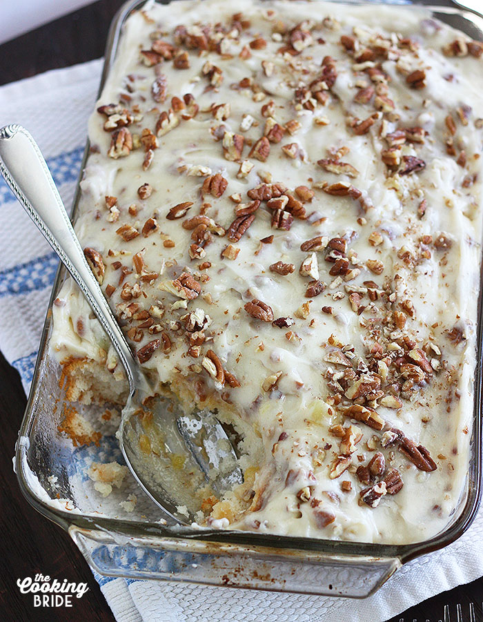 overhead shot of Pineapple Poke Cake in a pyrex dish on a blue and white towel