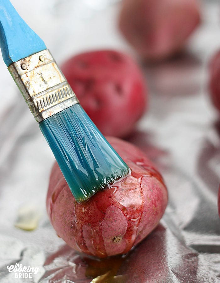 blue brush coating a red potato with olive oil