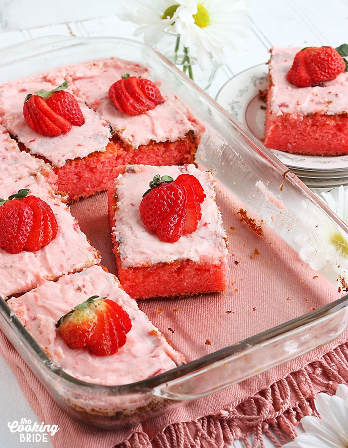 cut slices of strawberry sheet cake in a glass baking dish