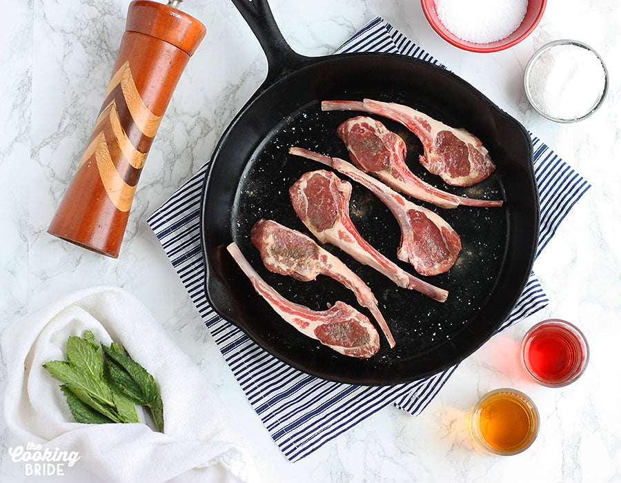 uncooked lamb chops in a skillet surrounded by recipes ingredients