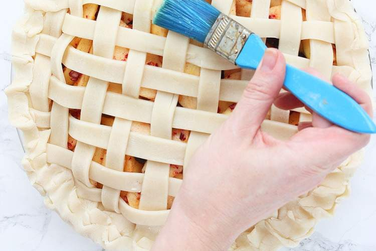brushing egg wash on the lattice pie crust