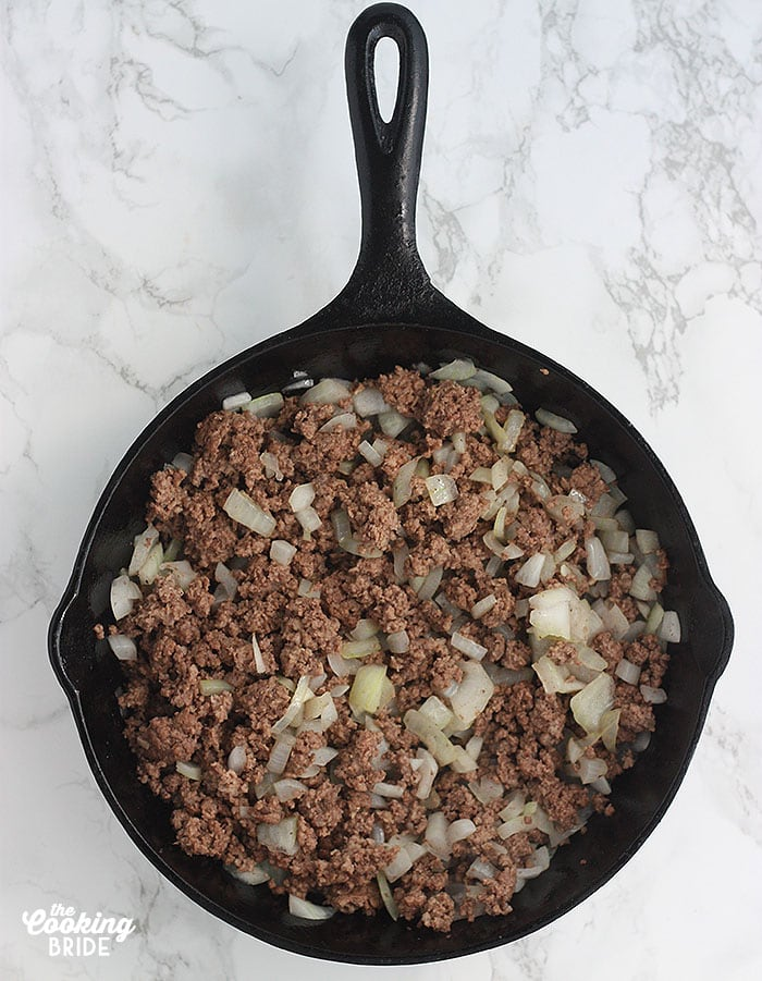 cast iron skillet with cooked hamburger and chopped onion