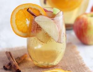 clear glass of apple cider sangria filled with apple slices and garnished with an orange and cinnamon stick