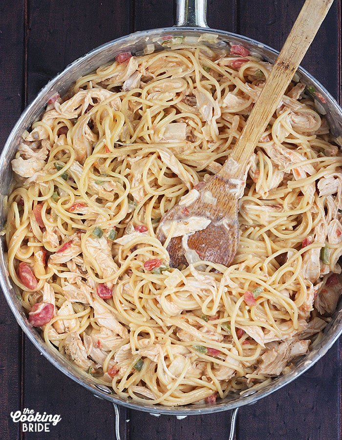 spaghetti noodles mixed with cheese, vegetables and rotel tomatoes in a large skillet