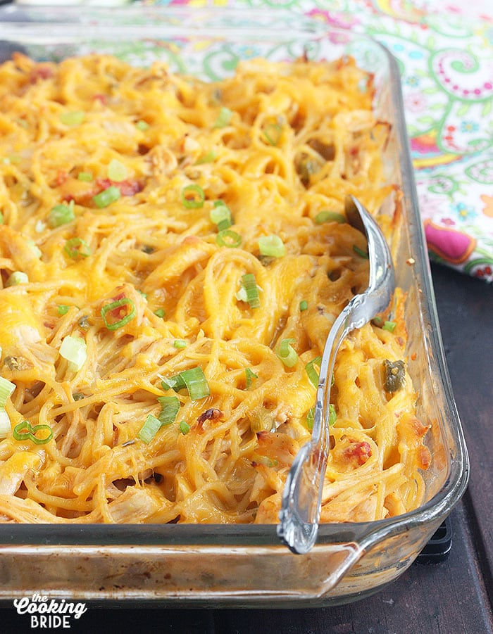 clear pyrex dish of baked chicken spaghetti with a metal serving spoon