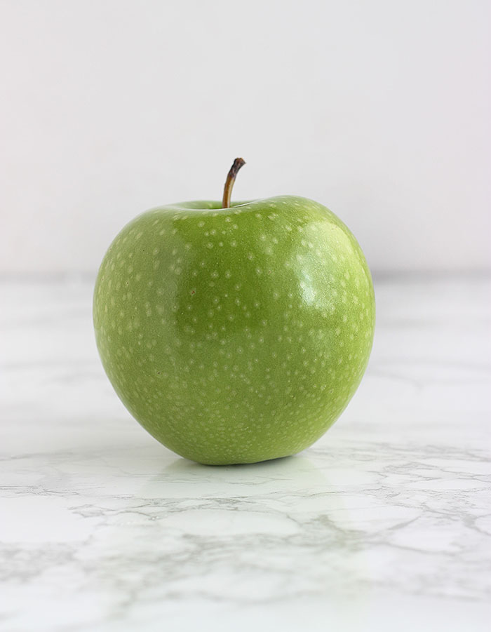 green Granny Smith apple on a white background
