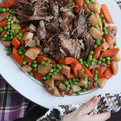 two hands laying a white platter with roast and veggieson a table