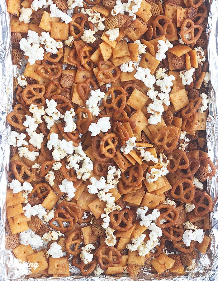 snack mix dry ingredients spread out on a foil lined baking sheet