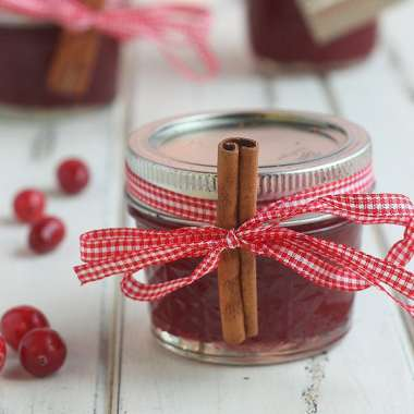 Small jar of strawberry cranberry jam decorated with a checkered ribbon and a stick of cinnamon