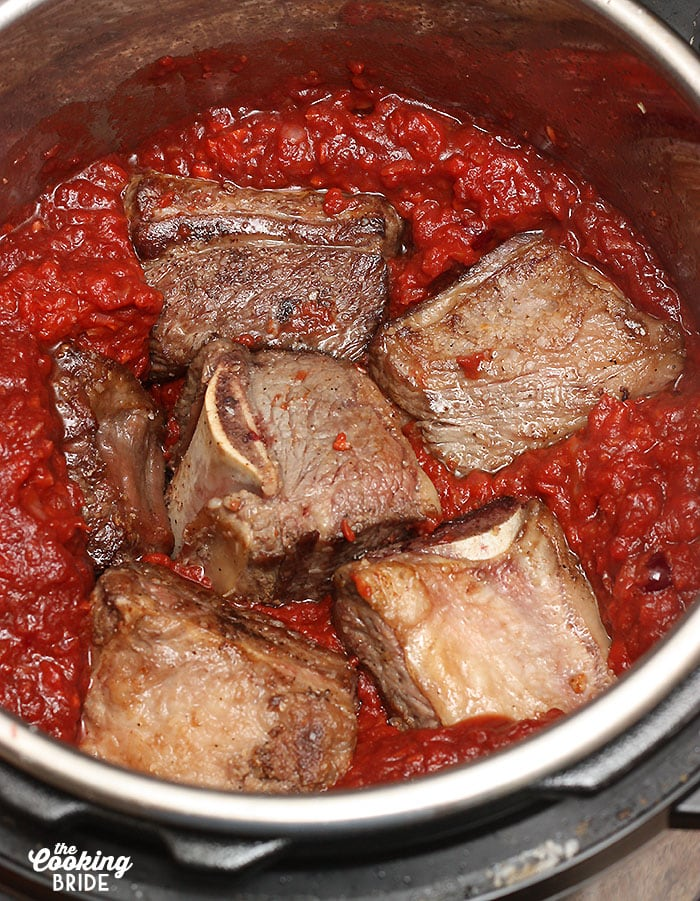 Nestling the browned shortribs in the tomato sauce and vegetables