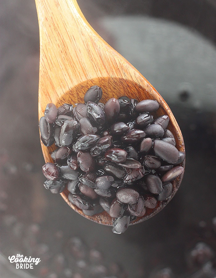 close up of soaked black beans on a wooden spoon