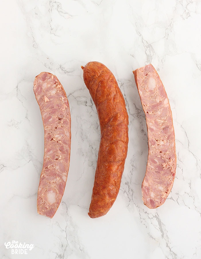 sliced andouille sausage on a white marble background