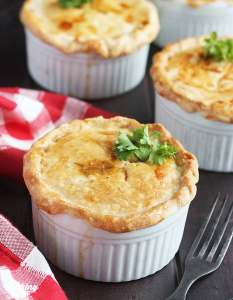 three baked crawfish pies on a wooden background with a red plaid napkin