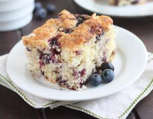 slice of blueberry breakfast cake on a white plate sitting on a white and green napkin
