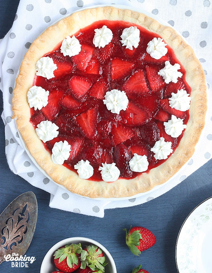 whole strawberry pie on a white and gray polka dotted napkin with a metal cake spatula and a small bowl of strawberries on a blue background