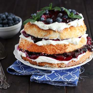 blueberry icebox cake garnished with mint leaves on a white plate served on a blue and white napkin with a silver cake server and a small bowl of blueberries in the background