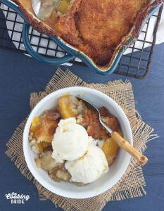 overhead shot of peach cobbler topped with two scoops of vanilla ice cream in a white bowl, dish of baked cobbler cools on a baking rack in the background