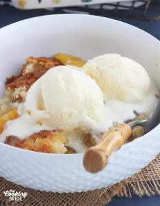 close up shot of peach cobbler topped with two scoops of vanilla ice cream in a white bowl