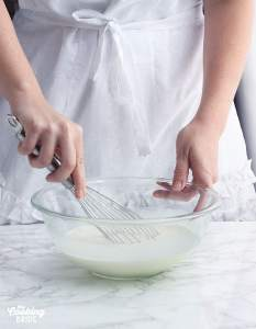 whisking the heavy cream into the milk and sugar