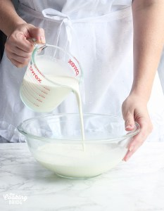 pouring heavy cream into a glass mixing bowl with milk and sugar