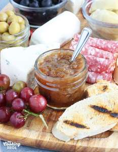 small jar of fig preserves on a meat and cheese tray