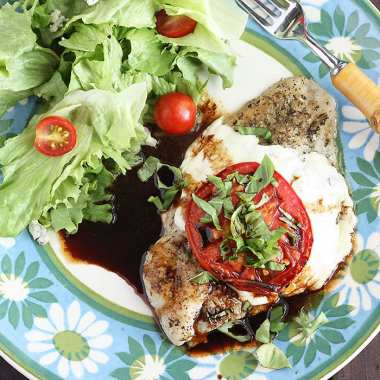 Caprese baked catfish fillet and a simple salad on a blue and green floral plate with a fork on the side