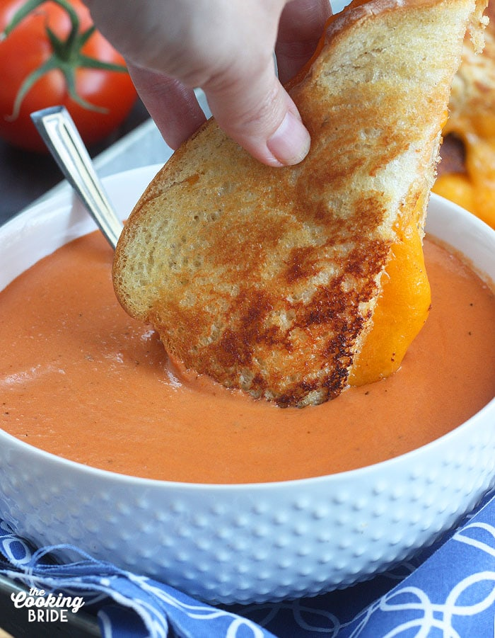 Dipping a wedge of grilled cheese sandwich into a bowl of cream of tomato soup