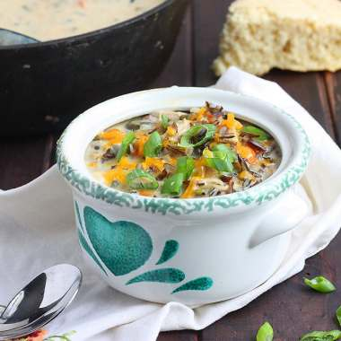 poblano chicken chowder in a green and white bowl garnished with green onions