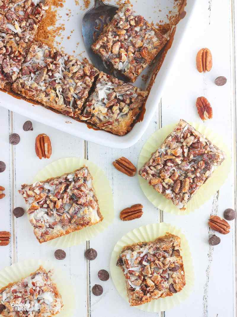 Over head shot of four Hello Dolly Bars on yellow wrappers surrounded by chocolate chips, pecans and a pan of cut bars to the side