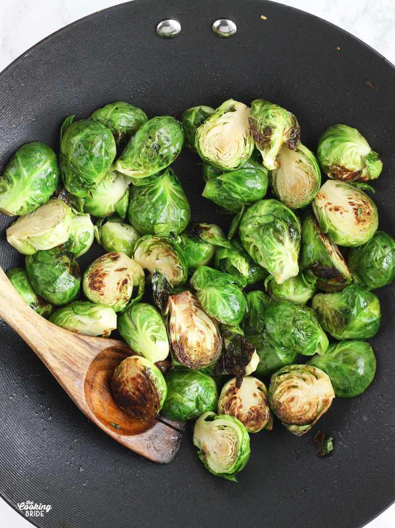 lightly charred Brussels sprouts cooking in a wok with a wooden spoon