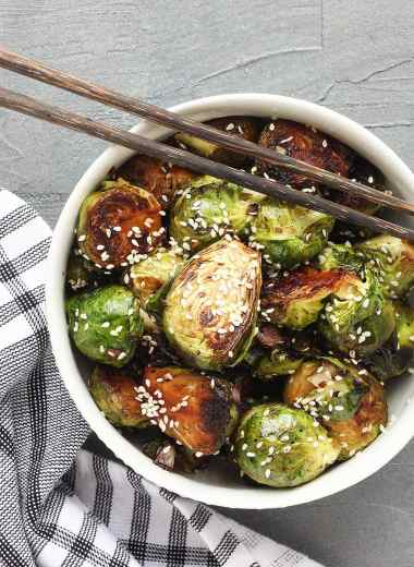 Overhead shot of Stir fried Brussels sprouts garnished with sesame seeds in a white bowl with wooden chopsticks resting on the side of the bowl.
